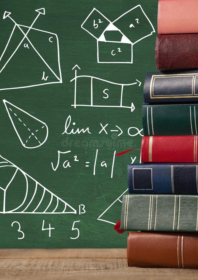 Los libros en el escritorio con los gráficos de la pizarra de la matemáticas diagrams fotos de archivo libres de regalías