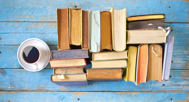 Los libros multicolores, taza de café, ponen completamente en la tabla de madera vieja, lectura, educación, literatura, aprendien imágenes de archivo libres de regalías