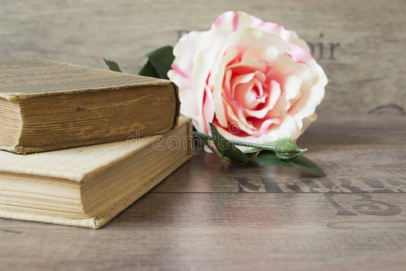Los libros viejos y la flor subieron en un fondo de madera Fondo floral romántico del marco Imagen de las flores que mienten en u foto de archivo