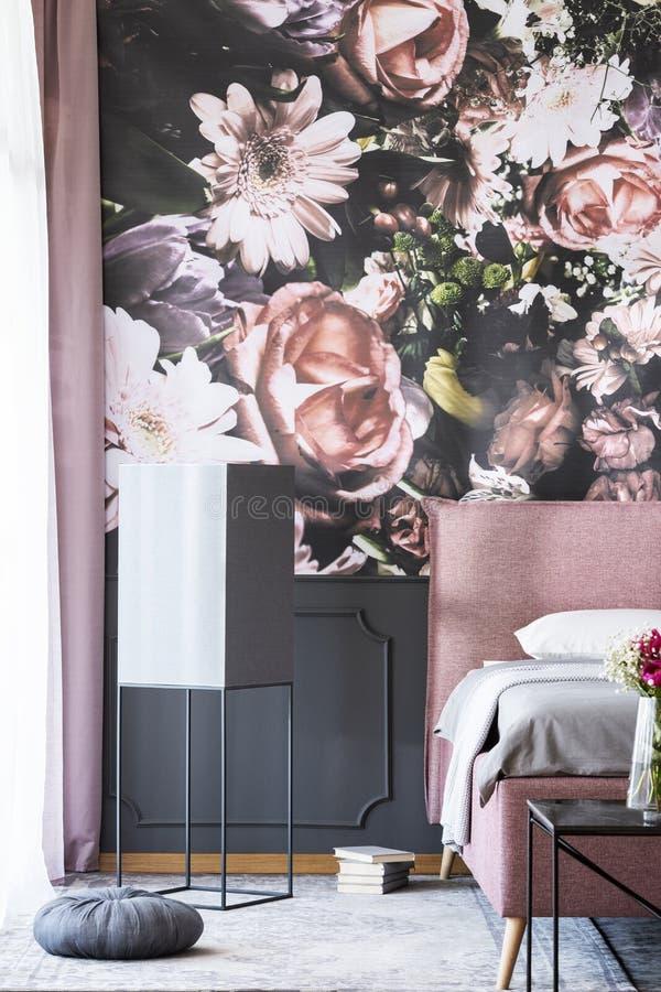 Los libros y la almohada gris al lado de la cama rosada en interior modelado del dormitorio con las flores wallpaper Foto verdade fotografía de archivo libre de regalías