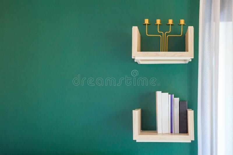 Los libros y la palmatoria en el estante adornan en una pared verde i fotos de archivo libres de regalías