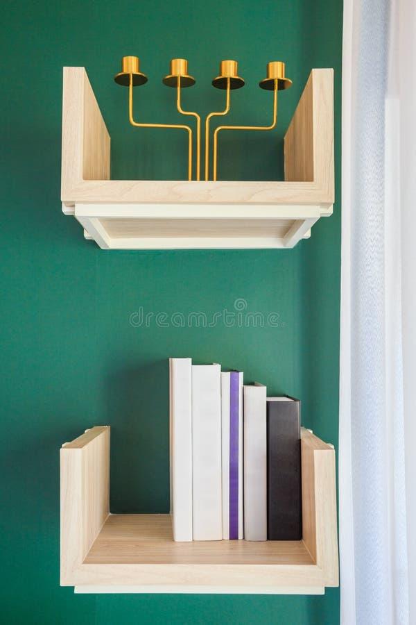 Los libros y la palmatoria en el estante adornan en una pared verde i foto de archivo