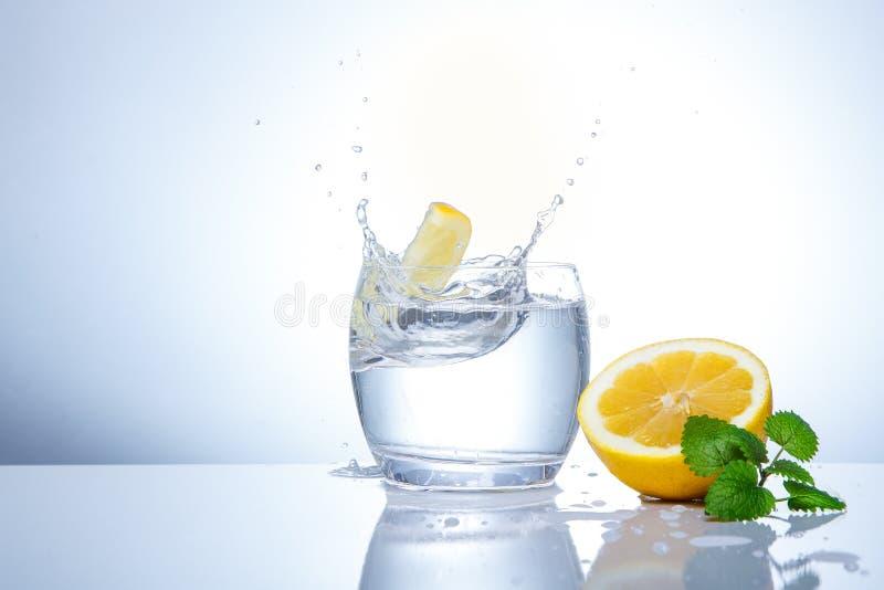 Los limones amarillos en un vidrio y salpican del agua Comida sabrosa y sana Bebidas estacionales foto de archivo