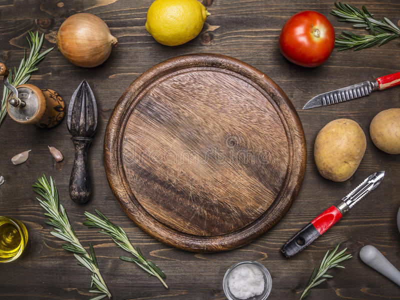 Los limones, tomates, cebollas, patatas, romero, cuchillo para pelar las patatas pusieron alrededor del texto redondo del lugar d imagen de archivo libre de regalías
