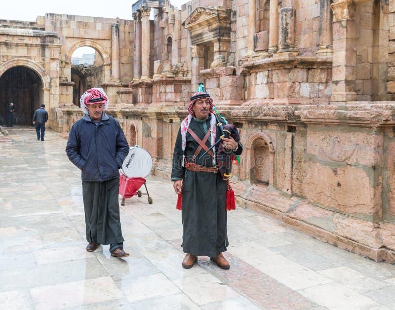 Los músicos bajo la forma de legión jordana aguardan a turistas en teatro meridional en ruinas de la ciudad romana Jerash - Geras foto de archivo libre de regalías