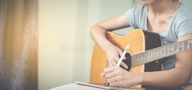 Los músicos de sexo femenino tocan la guitarra y escriben canciones usando la tableta Th foto de archivo libre de regalías