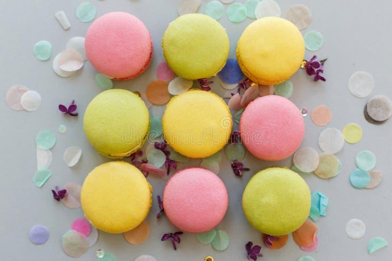 Los macarons coloridos en el papel gris en colores pastel de moda con la lila florecen imagen de archivo