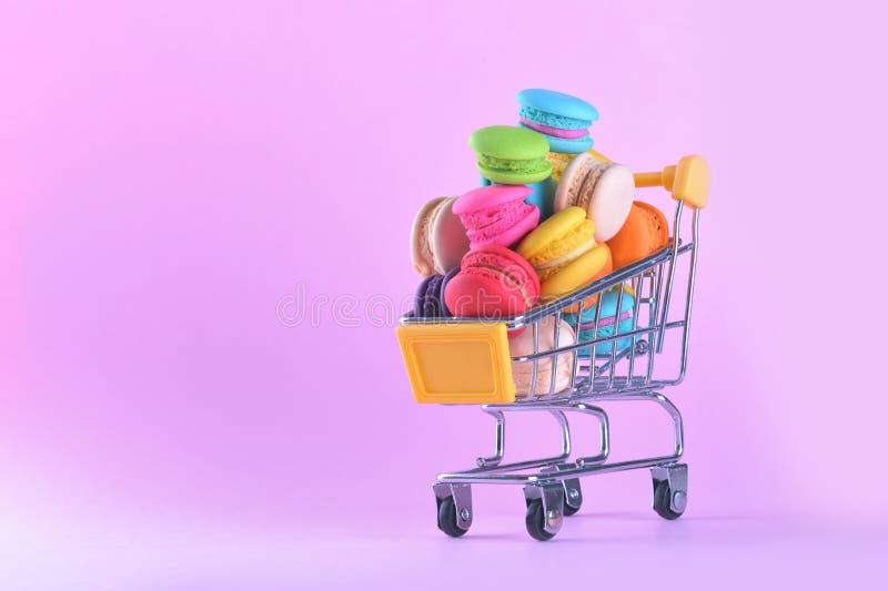 Los macarons o los macarrones coloridos en dulce del postre del carro de la compra sean imagenes de archivo