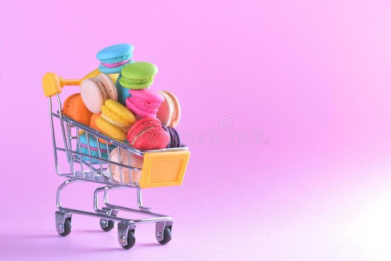 Los macarons o los macarrones coloridos en dulce del postre del carro de la compra sean imagen de archivo libre de regalías