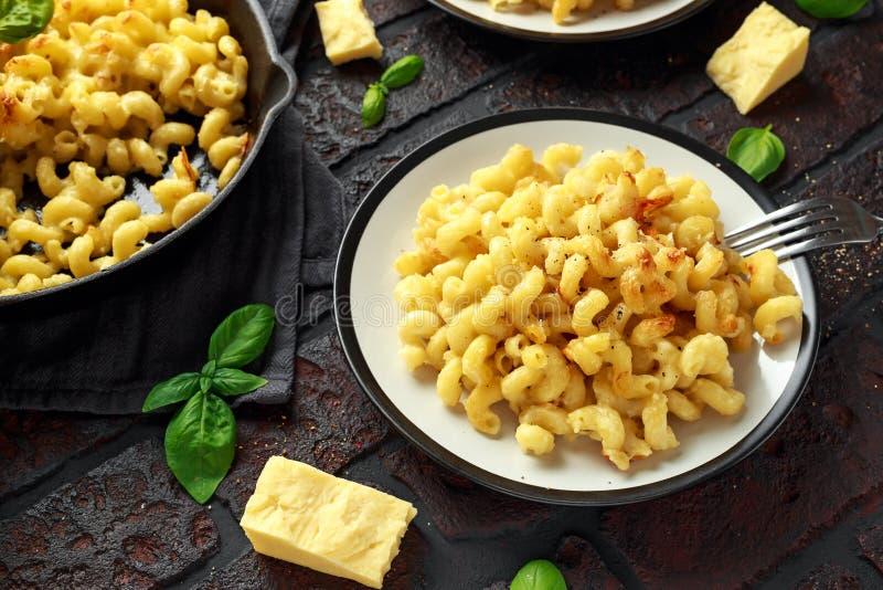 Los macarrones con queso cocidos hechos en casa con Cheddar sirvieron en la placa fotos de archivo libres de regalías