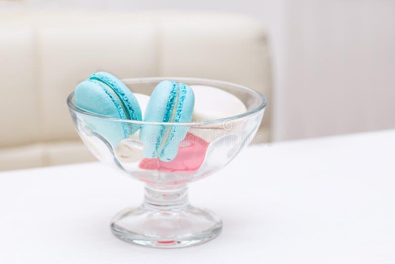 Los macarrones del caramelo mienten en un florero de cristal para los dulces en una tabla blanca imágenes de archivo libres de regalías