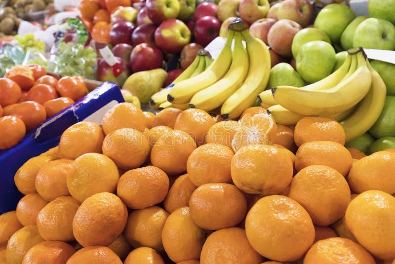 Los mandarines, plátanos, manzanas mienten en el contador del mercado para la venta imagenes de archivo