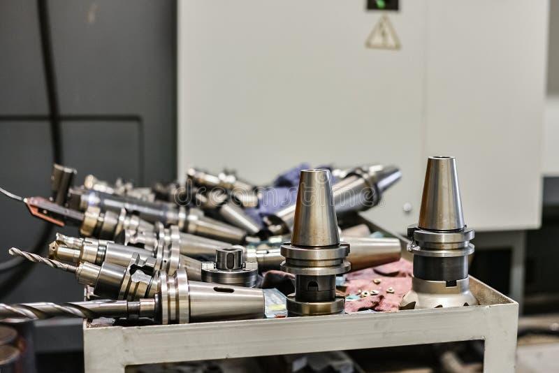 Los mandriles y los accesorios para la fresadora del CNC están situados en la máquina cerca del equipo industrial Taladros, corta imagenes de archivo