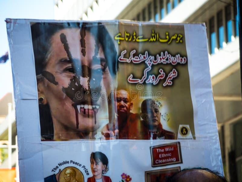 Los manifestantes muestran la imagen del cartel de Aung San Suu Kyi con la cara malvada para exigir la O.N.U para parar el matar  imagenes de archivo