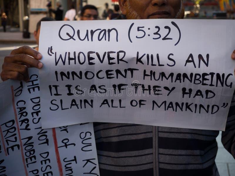 Los manifestantes muestran las palabras de dios por 5:32 santo del verso del Quran para exigir la O.N.U para parar el matar del g imagen de archivo libre de regalías