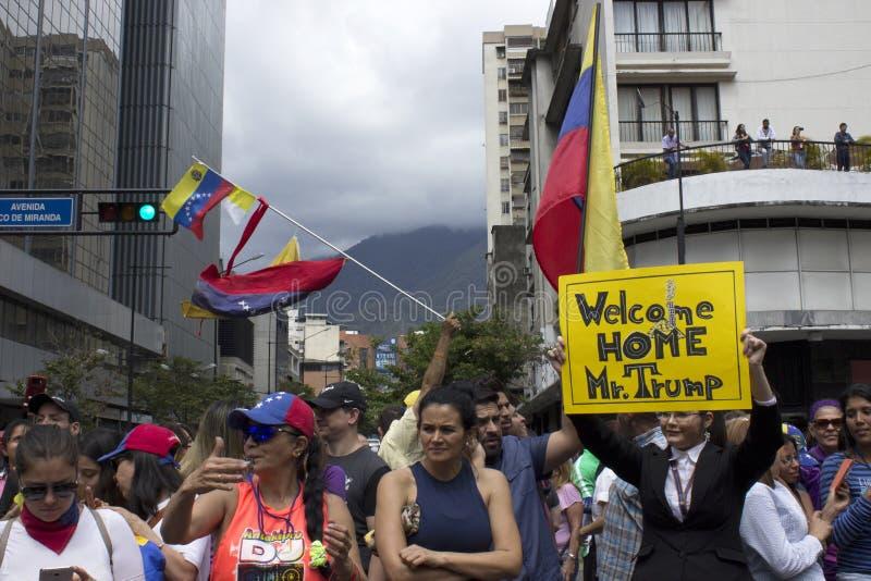 Los manifestantes sostienen banderas que dan la bienvenida a los movimientos agresivos de Donald Trump en Venezuela imágenes de archivo libres de regalías