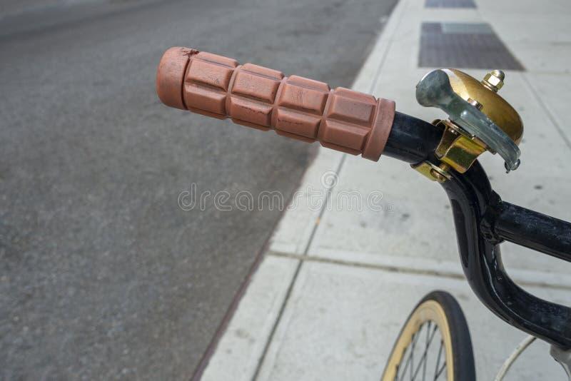 Los manillares de la bicicleta de la calle de la acera con oro del hockey shinny revisten la campana con cobre fotografía de archivo libre de regalías
