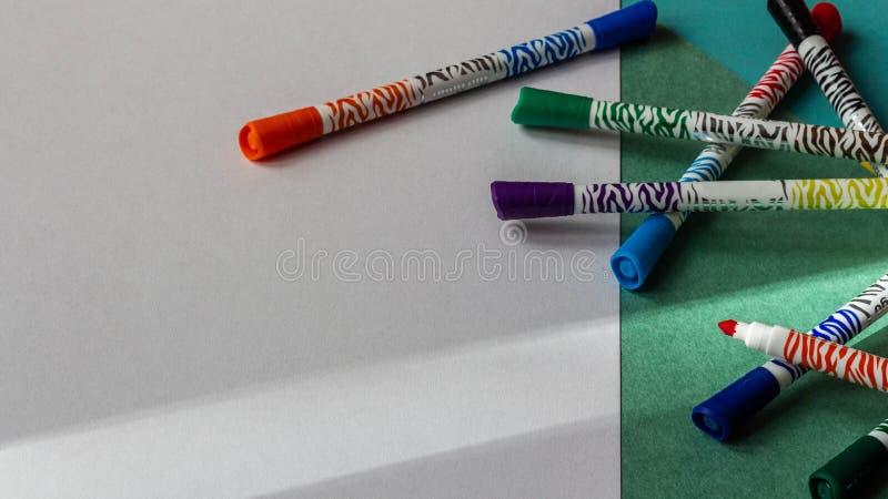 Los marcadores multicolores mienten en el fondo de la cartulina coloreada y del primer del Libro Blanco fotos de archivo libres de regalías