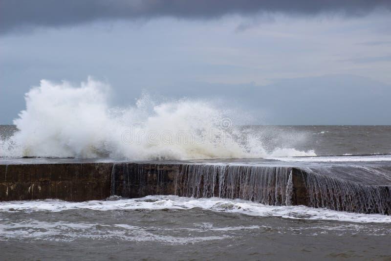 Los mares tempestuosos se rompen sobre la pared de mar en el agujero largo en Bangor, condado abajo durante los mares agitados en fotografía de archivo libre de regalías