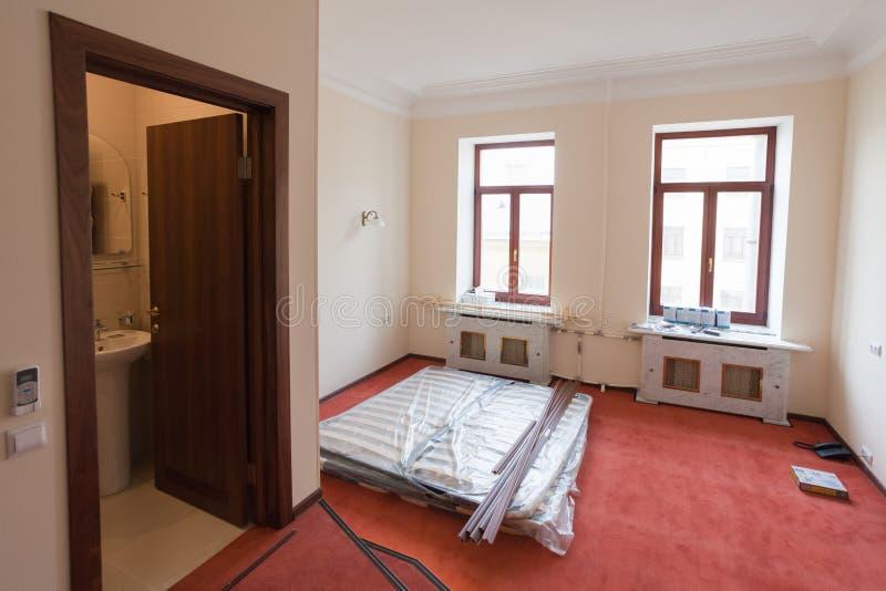 Los materiales, los muebles y el teléfono de construcción están en el piso del apartamento en el hotel durante la construcción in imagenes de archivo