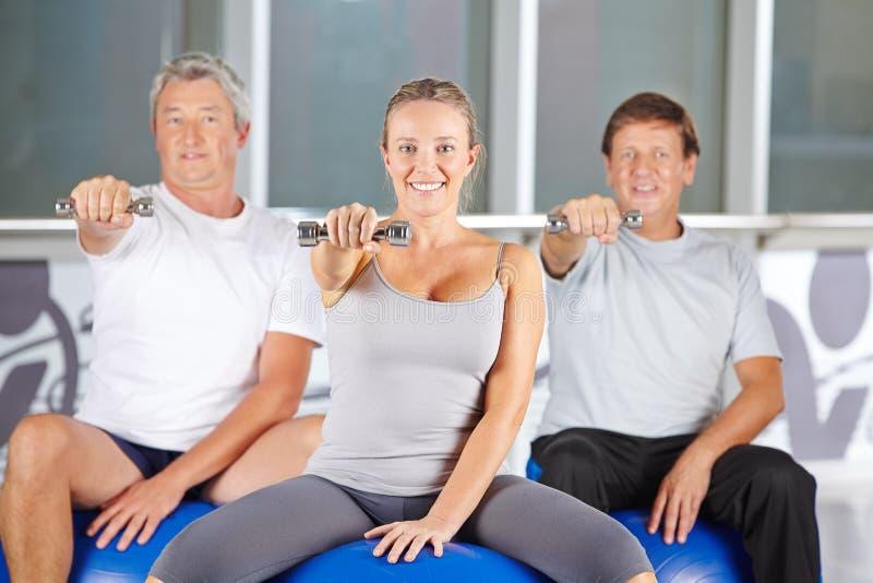 Los mayores ejercitan con pesas de gimnasia en el centro de aptitud imagenes de archivo