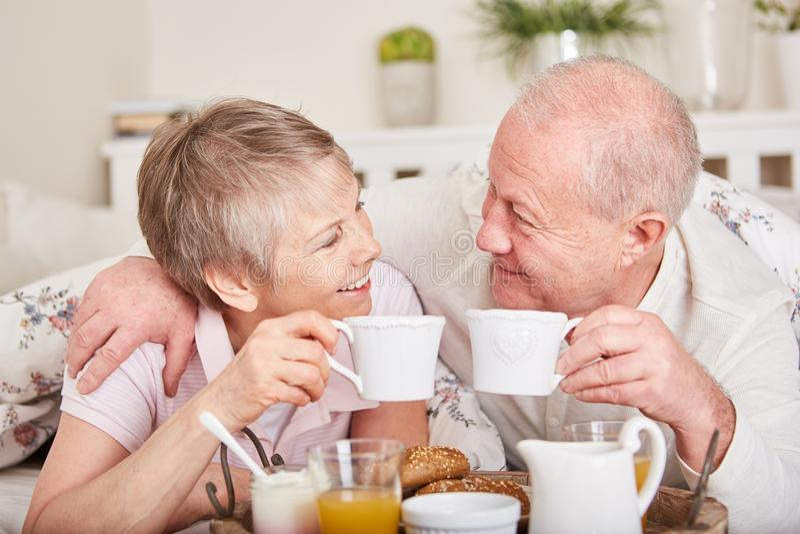 Los mayores en amor desayunan juntos fotos de archivo