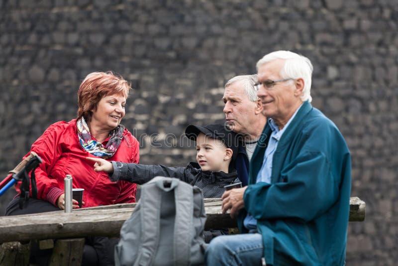 Los mayores y el niño en la familia disparan la reclinación al aire libre foto de archivo libre de regalías