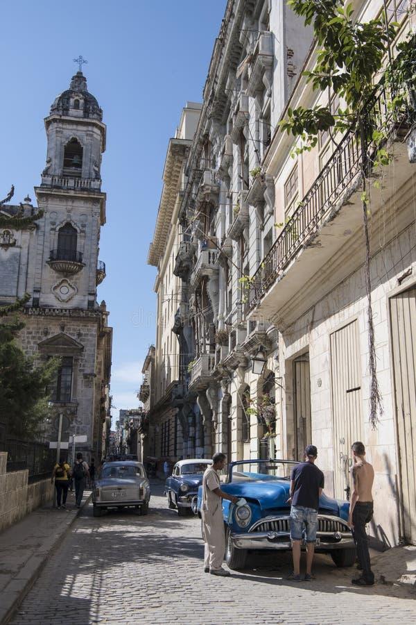 Los mecánicos intentan reparar el coche clásico en la calle de La Habana imagen de archivo libre de regalías