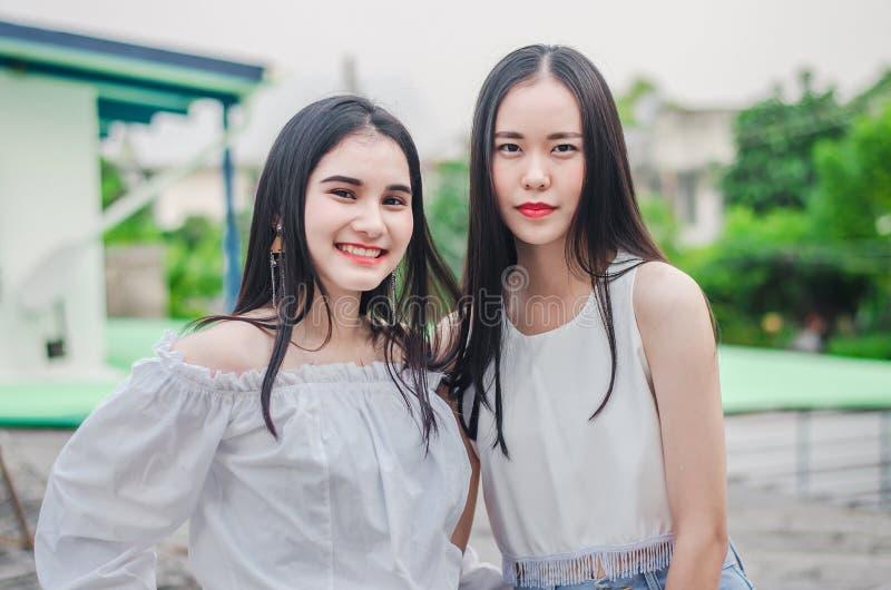 Los mejores amigos asiáticos felices jovenes de las muchachas sonríen uniéndose y divirtiéndose que mira la cámara foto de archivo libre de regalías