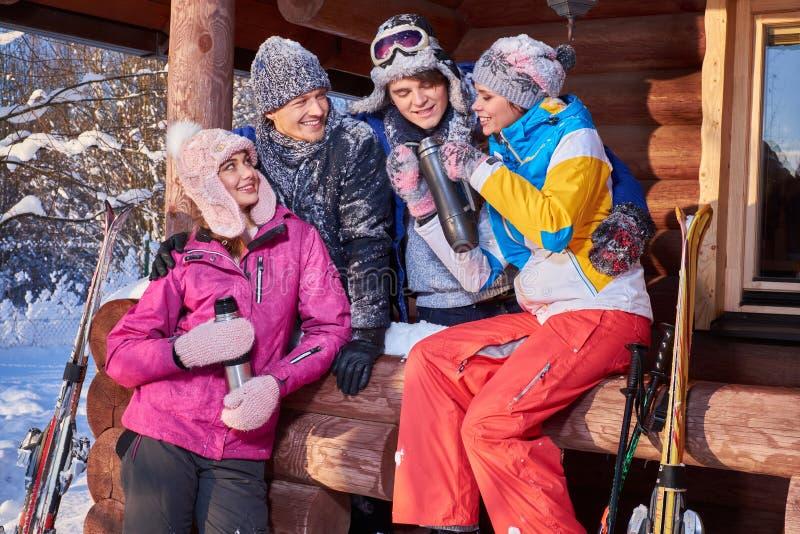 Los mejores amigos pasan vacaciones de invierno en la cabaña de la montaña foto de archivo libre de regalías