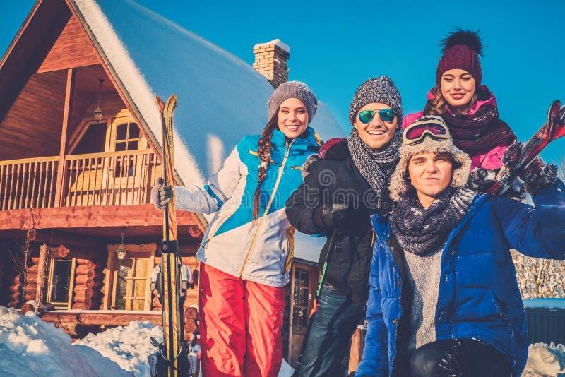 Los mejores amigos pasan vacaciones de invierno en la cabaña de la montaña imágenes de archivo libres de regalías