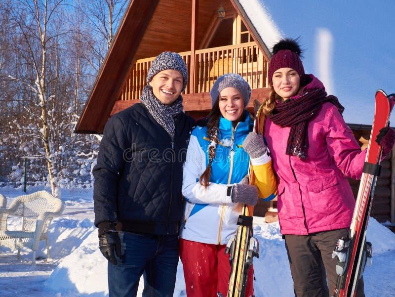Los mejores amigos pasan vacaciones de invierno en la cabaña de la montaña imagen de archivo