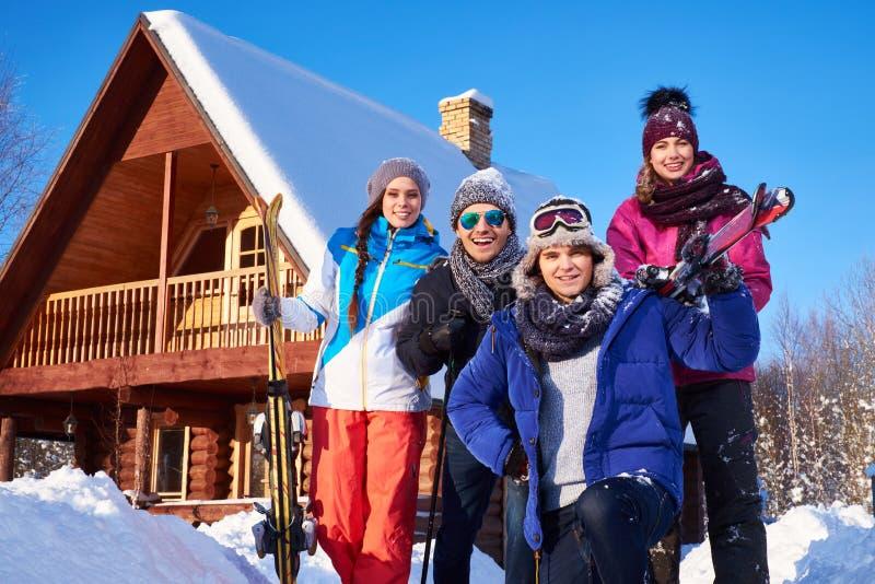 Los mejores amigos pasan vacaciones de invierno en la cabaña de la montaña fotografía de archivo