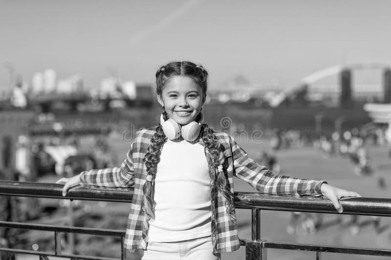 Los mejores apps de la m?sica que merecen a para escuchar El ni?o de la muchacha escucha m?sica al aire libre con los auriculares fotografía de archivo libre de regalías