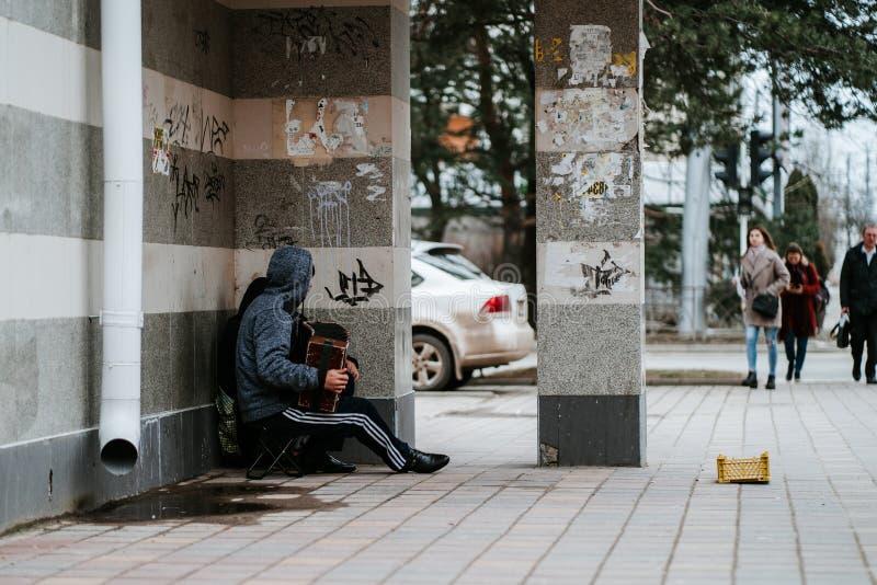 Los mendigos hambrientos sin hogar del músico con el acordeón piden limosnas en la calle cerca de la pared fotos de archivo