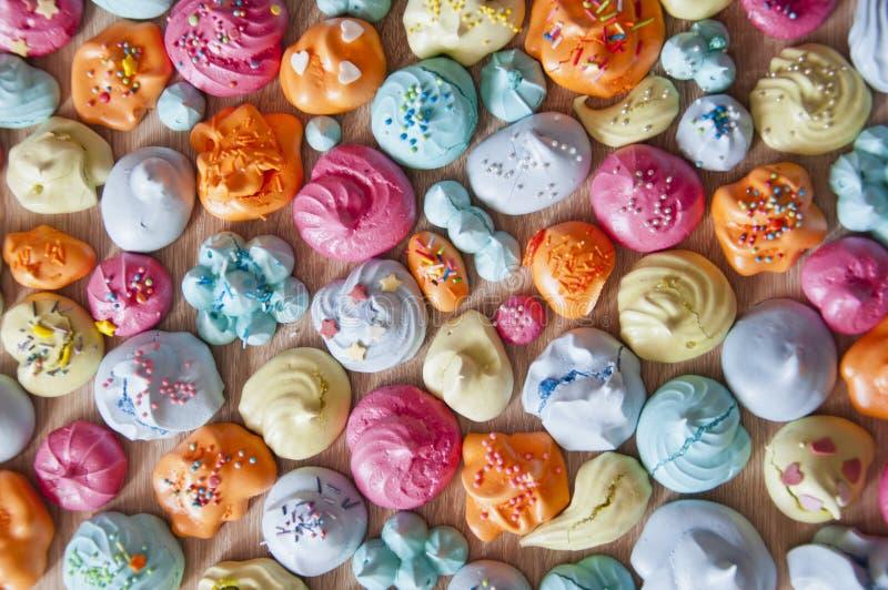 Los merengues con colorido asperjan, endecha plana Merengue de Macaron con el desmoche colorido Celebración de la fiesta de cump imagen de archivo libre de regalías