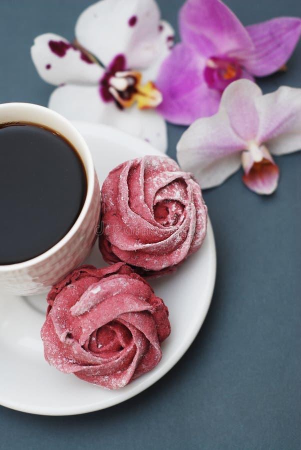 Los merengues y la taza de café rosados dulces en fondo del gris azul con la orquídea florece Fondo de la primavera con el espaci fotografía de archivo libre de regalías