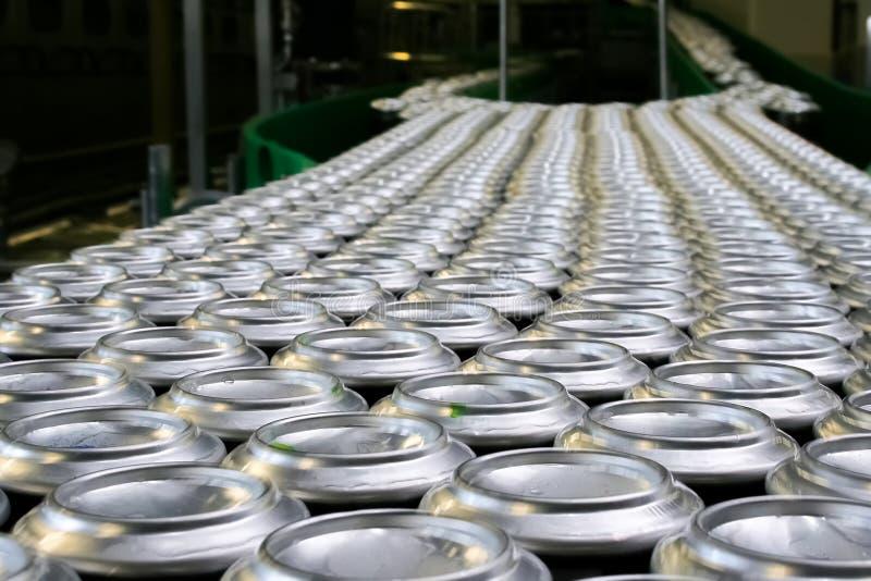 Los millares de latas de aluminio de la bebida en transportador alinean en la fábrica fotos de archivo libres de regalías
