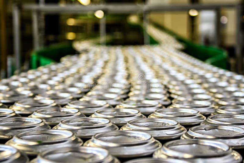 Los millares de latas de aluminio de la bebida en transportador alinean en la fábrica imagenes de archivo
