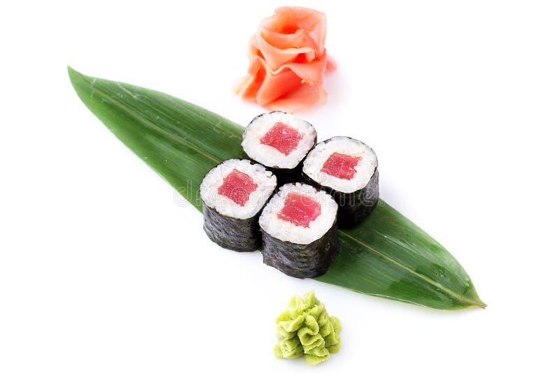 Los mini-rollos frescos deliciosos con el atún en un plátano hojean Rollos de sushi en un fondo blanco con el jengibre y el wasab imágenes de archivo libres de regalías