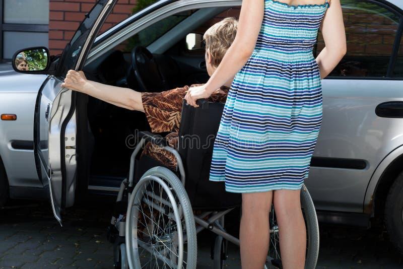 Los minusválidos de ayuda de la mujer consiguen en el coche imágenes de archivo libres de regalías