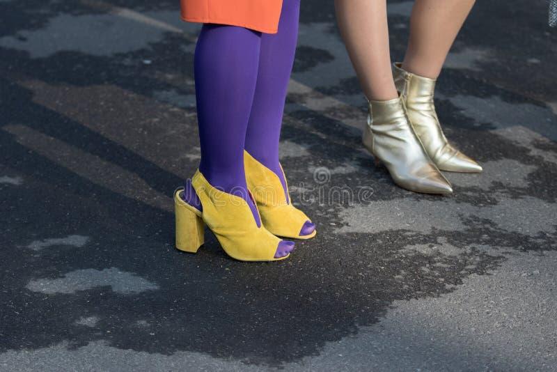 Los modelos llevan un par de zapatos amarillos con los talones y las botas púrpuras del calcetín y de oro del tobillo foto de archivo