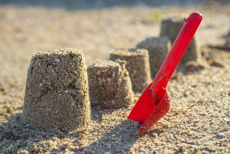 Los moldes hicieron de la arena mojada con la pala roja en la playa Juguete de la playa de los niños, pala en la playa arenosa fotos de archivo