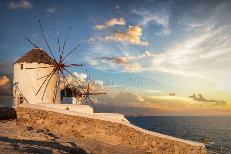 Los molinoes de viento situados sobre la ciudad de la isla de Mykonos en el tiempo de la salida del sol fotografía de archivo