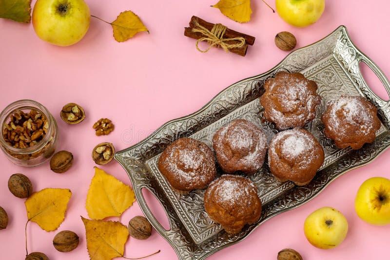 Los molletes hechos en casa con las manzanas y las nueces arreglaron en una bandeja en un fondo rosado foto de archivo libre de regalías