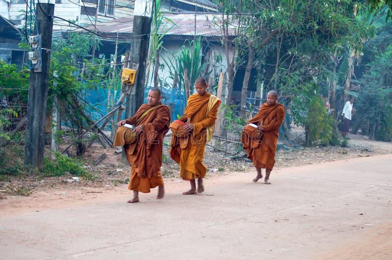 Los monjes caminan en la madrugada en el pueblo de Isan en la provincia de Sakon Nakhon, Tailandia fotografía de archivo