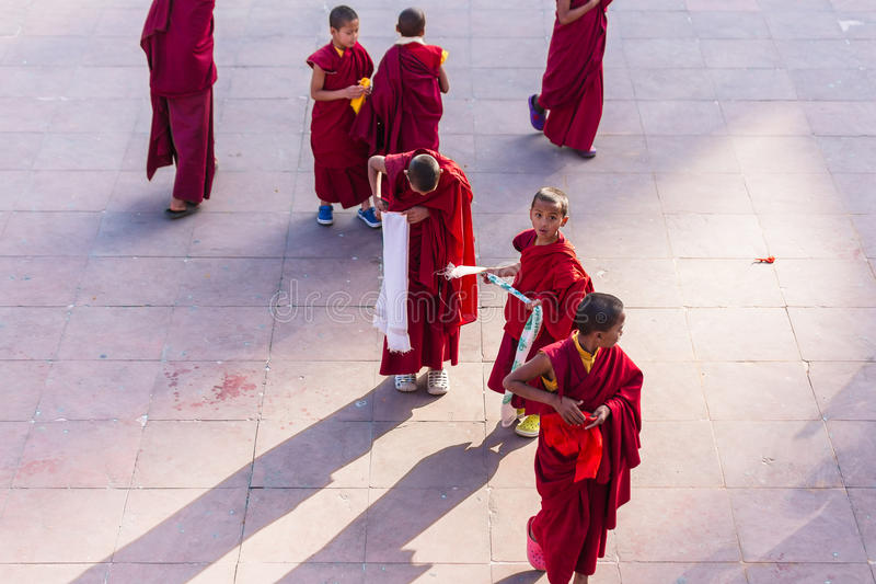 Los monjes jovenes tibetanos caminan y juegan delante del monasterio de Rumtek después de monje de alto nivel llegaron cerca de G imagenes de archivo