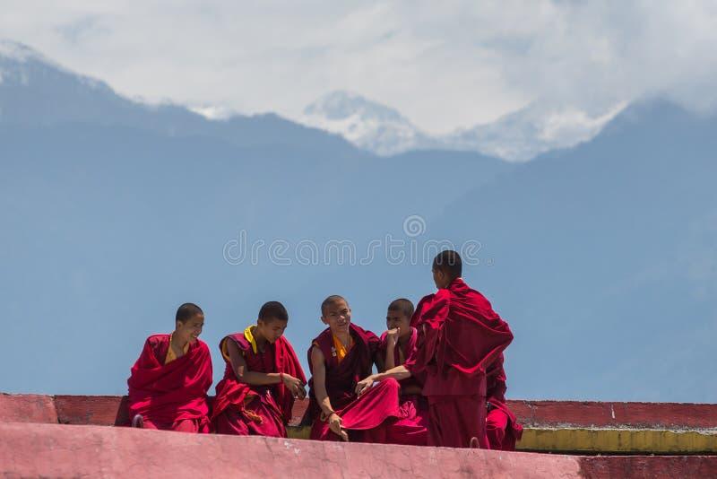 Los monjes tibetanos descansan en el nivel superior del monasterio de Rumtek cerca de Gangtok con las montañas de Himalaya en el  fotos de archivo libres de regalías