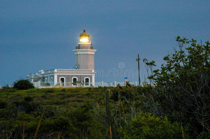 Los Morrillos Lighthouse. Lit up during dusk at the southwestern corner of the island of Puerto Rico stock image