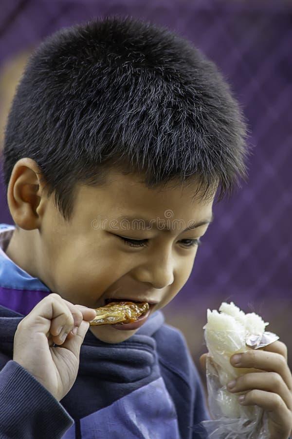 Los muchachos asiáticos están comiendo el arroz pegajoso y la carne asada de cerdo, la comida es simple y popular comer el desayu fotografía de archivo